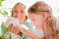 Smiling mother and daughter looking at pink flowers