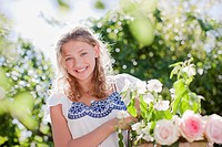 Smiling girl holding basket of flowers in garden