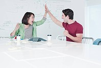 Excited business people giving high five in conference room