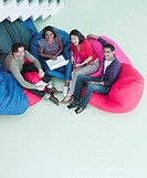 Smiling business people sitting in bean bag chairs (thumbnail)