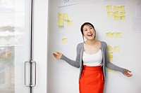 Smiling businesswoman with arms outstretched in front of whiteboard with adhesive notes