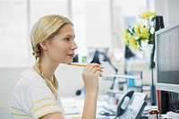 Businesswoman holding pencil and looking at computer monitor