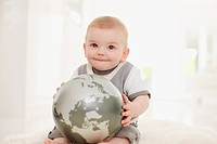 Smiling baby holding globe on floor