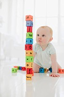 Baby on floor looking at stacked wood blocks