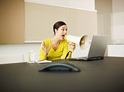 Businesswoman yelling at laptop with bullhorn in conference room (thumbnail)