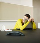Smiling businesswoman hugging laptop in conference room (thumbnail)