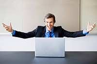 Excited businessman with arms outstretched looking at laptop