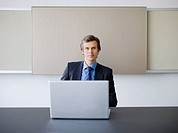 Confident businessman sitting at laptop