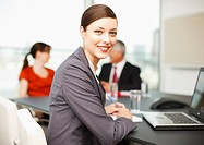 Smiling businesswoman sitting at laptop in conference room