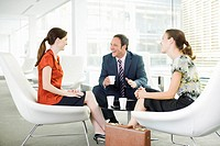 Smiling business people having a meeting and drinking coffee