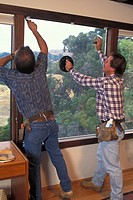 Workmen in home installing glass window