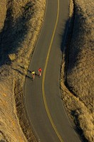 Bicycle riders climbing up hill on winding road in Northern California