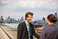 Smiling business people on balcony overlooking city