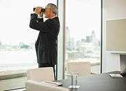 Businessman with binoculars looking out office window