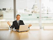 Happy businessman gesturing and looking at computer in conference room