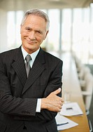 Smiling businessman with arms crossed in empty conference room