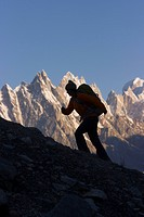 A silhouette of a woman hiker on the Biafo glacier in the Karakoram Himalaya in Pakistan