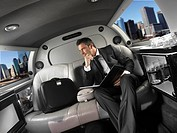 Businessman sitting in the back seat of a limousine
