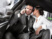 Businessman and businesswoman sitting in the back seat of a limousine, woman flirting with him