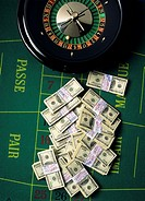 wads of 100 us dollars & roulette wheel