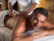 Man getting herbal compress treatment