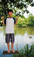 Boy standing on swing by lake