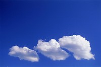 Family of three clouds passing through clear blue skies