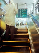 Man going up on escalator at airport, blurred motion