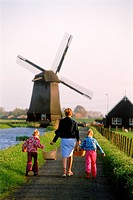 Mother and children with baskets walking home in Holland near windmill and canal