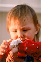 Young girl with white mouse on her arm