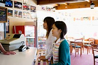 Two young women ordering food at fast food restaurant