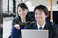 A young woman and a mid adult man sitting in a bus