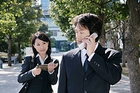 A mid adult businessman talking over mobile phone and young businesswoman standing behind