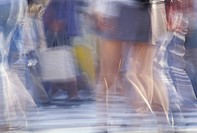 Blurred legs of people crossing street