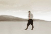 Businessman looking at watch while walking across barren desert landscape