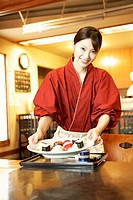 Waitress serving sushi