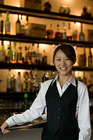Waitress standing in front of bar counter