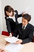 Young businesswoman giving document to colleague