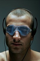 Men with mask on eyes listening to music