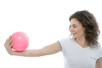 Studio shot of young woman exercising with pink ball