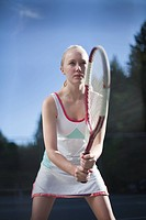 Young female tennis player waiting to return serve, profile