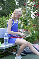 Young female tennis player examining racquet