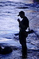 Silhouette of young man fly fishing on the Truckee River, California, USA