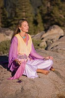 A blonde woman in flowing robes sitting in meditation on a rock