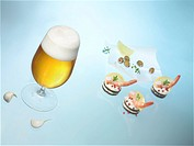 Glass of beer and prawns on pumpernickel rounds