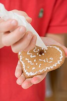 Child decorating biscuit with piping bag
