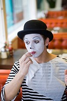 Young man, painted face, mime, smiling