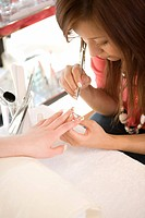 Beautician decorating finger nails