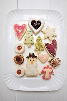 Assorted decorated Christmas biscuits on white platter