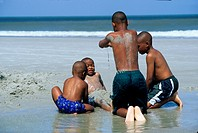 African American boys playing in sand at beach Jacksonville Florida